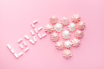 Valentine's day concept. A heart made of pink and white Bizet and the word love made from marshmallows on a pink background. Top wiev