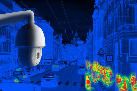 The concept of video surveillance and security technology. CCTV camera on the background of the city road with cars, pedestrian crossing and definition people. Night tint
