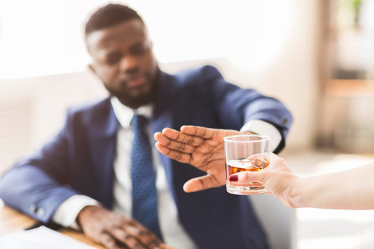 Businessman saying no to glass of whiskey offered by colleague