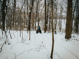 A horizontal, landscape frame of a four wheeler quad riding through the snow covered country woods after a severe winter storm. A partly cloudy sky shines on the covered trees, farm, and mountains.