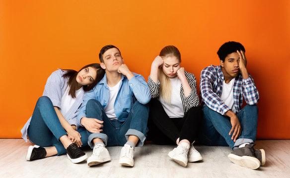 Bored classmates sitting over orange studio background