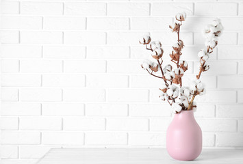 Beautiful cotton flowers in vase on wooden table against white brick wall, space for text