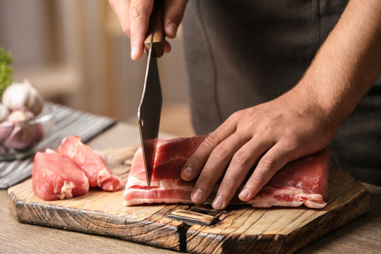 Man cutting fresh raw meat on table in kitchen, closeup