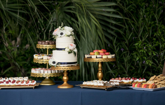 Dessert table with two tiered cake at wedding reception or party.