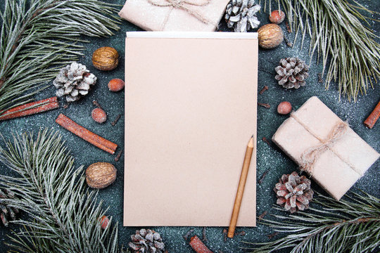 Christmas background with blank notebook surrounded by Christmas decorations. Letter to Santa or Christmas shopping list