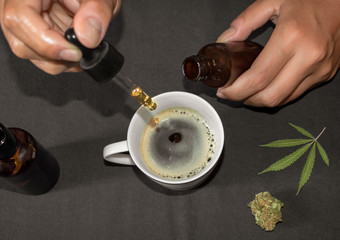 Pouring CBD tincture in a coffee cup, natural remedy of marihuana. Person using cannabis oil with a dropper in a table with marihuana leaf.
