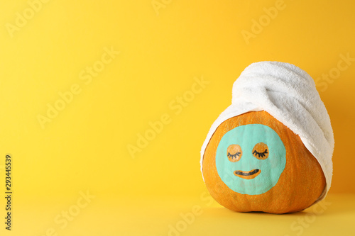 Pumpkin with facial mask and towel on yellow background, copy space