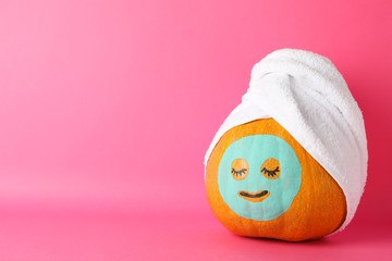 Pumpkin with facial mask and towel on pink background, copy space