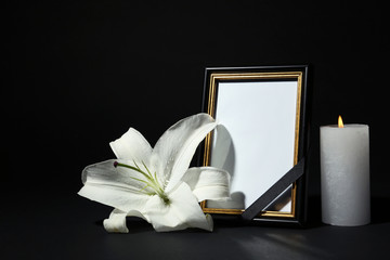 Funeral photo frame with ribbon, white lily and candle on dark table against black background....