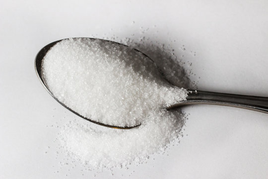 A high contrast spoonful of sugar on white background
