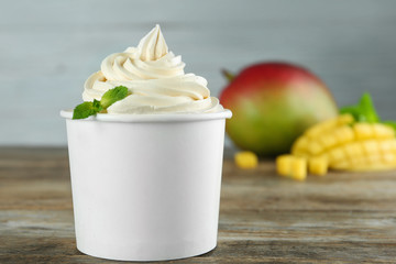 Cup with tasty frozen yogurt and mango on wooden table. Space for text
