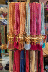 Hanging rosaries in different patterns and colors.
