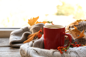 Cup of hot drink, sweater and autumn leaves on windowsill, space for text. Cozy atmosphere