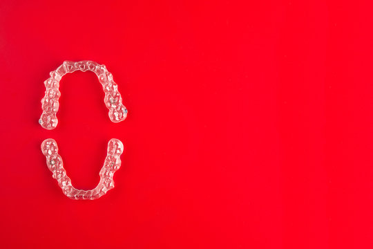 Top view of invisalign braces or invisible retainers on red background, new orthodontic equipment