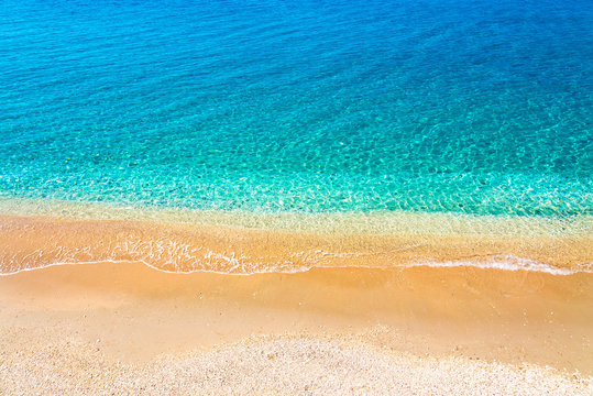 Top view of sandy beach and turquoise ocean water with small waves, beautiful summer sea background.