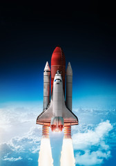 Wall Murals Nasa Space shuttle launch in outer space from Earth. Rocket on orbit of the planet. Border of blue sky with clouds and dark deep space. .Elements of this image furnished by NASA