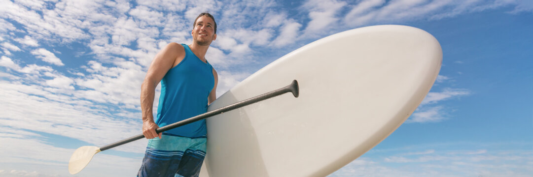 Paddle board SUP fit man carrying paddleboard on hawaii beach banner panorama. Fitness active lifestyle fun activity outdoors athlete.