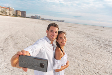 Wall Mural - Selfie vacation beach couple romantic honeymoon. Happy young woman and man taking photo with phone - newlyweds on holdiay.