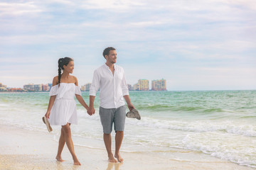 Wall Mural - Beach couple romantic sunset walk Asian woman and Caucasian man relaxing walking on Florida vacation beach travel holidays wearing white dress and linen clothes. Happy interracial relationship.