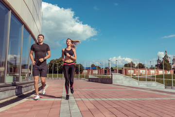 Young couple man woman, in summer, autumn spring in city, jogging, free space for motivation text, sportswear, top leggings, sneakers, active fitness lifestyle, outdoor sports exercise.