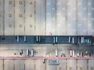 4k Aerial shot of trucks on warehouse parking terminal.