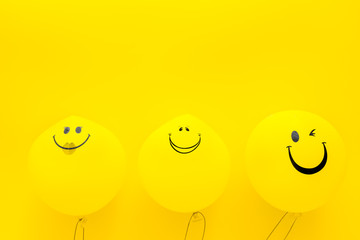 Happiness emotion. Yellow balloon with smile on yellow background top view space for text