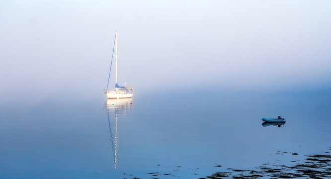 Beautiful shot of a boat coming out of the fog on the water at  Maine, USA