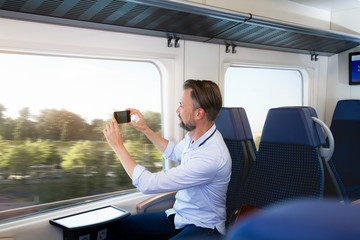Mature man sitting in a train, taking pictures with his smartphone