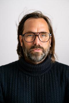 Portrait of confident mature man wearing eyeglasses against white background