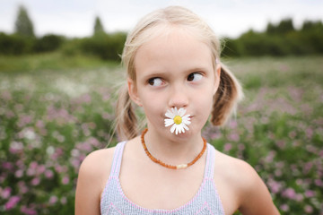 Girl with chamomile flower in her mouth