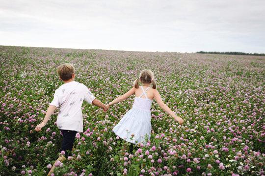 Two smiling children running over clover field