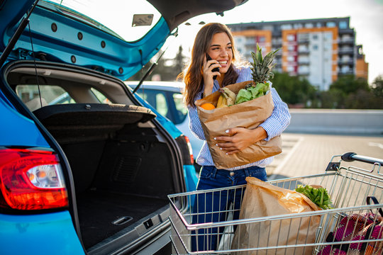 Beautiful young woman shopping in a grocery store/supermarket, putting the groceries into her car in the parking lot, looking around and talking with smartphone.