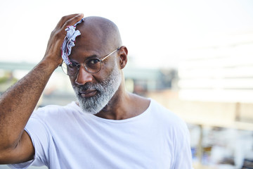 Portrait of mature man wiping his bald on hot summer day