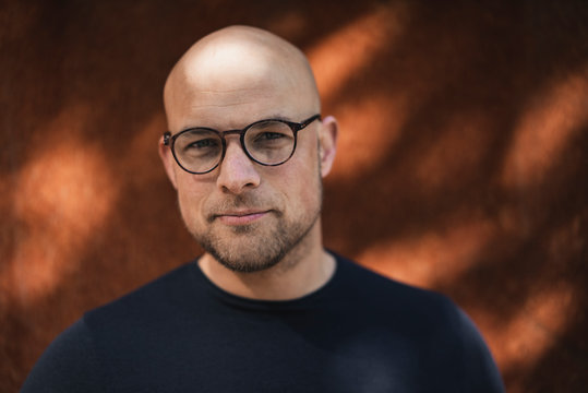 Portrait of bald man with beard wearing glasses