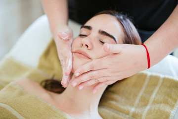 Young woman receiving facial beauty treatment in a spa