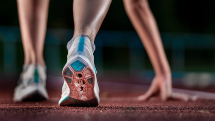 Legs of female, athlete running on tartan track