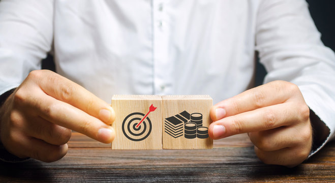 Businessman collects wooden blocks with the image of the goal and money. The concept of doing business and finance. Setting goals and objectives for maximum profit. Strategy and Planning