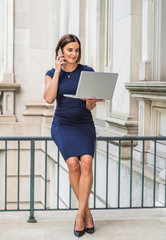 Young 40 years old Native American Businesswoman working in New York, wearing short sleeve dress, sitting on railing inside vintage office building, working on laptop computer, talking on cell phone..