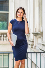 Young 40 years old Native American Businesswoman working in New York, wearing blue short sleeve dress, necklace, carrying laptop computer, standing in vintage office building, talking on cell phone..
