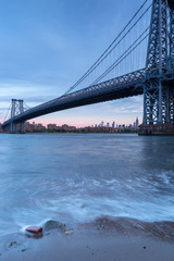 View on Williamsburg bridge and Midtown Manhattan from East river beach at sunrise.