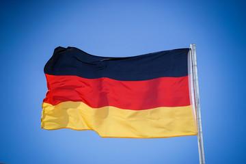 Die deutsche Flagge an einen Fahnenmast im Wind