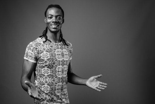 Young handsome African man against brown background