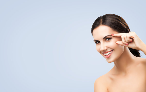 Skin care beauty concept picture. Portrait of happy smiling beautiful woman pointing brow or eye, touching skin, applying face cream, isolated over grey color background. Brunette model.