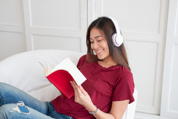 Asian woman listening music on headphone and reading book with relax pose at couch in living room...