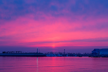 Beautiful pink sunset on the marina yacht harbor with tranquil waves.