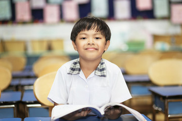 An Asian young boy studying happily and cheerfully in his classroom.