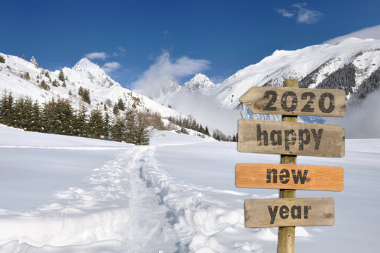 2020 happy new year written on a postsign in the snow on white mountain background