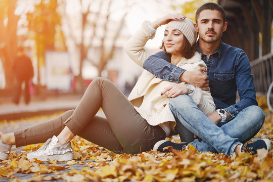 couple sitting on the ground in the city by the autumn leaves