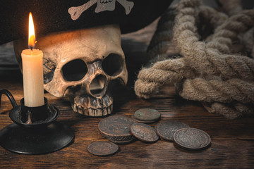 Human skull in a pirate hat, old coins, mooring rope and burning candle on brown wooden desk background.