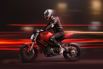 Motorcycle rider racing in red colors with motion blur
